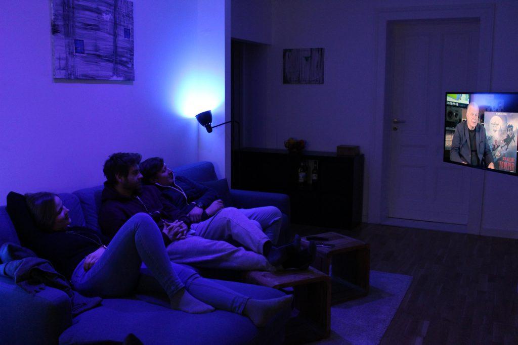 Alle Mitbewohner sitzen auf der Couch, das Licht leuchtet blau.